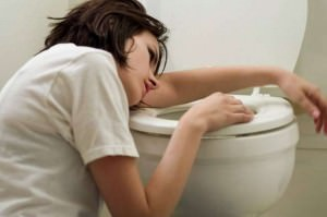 Sick woman throwing up into toilet food poisoning tests